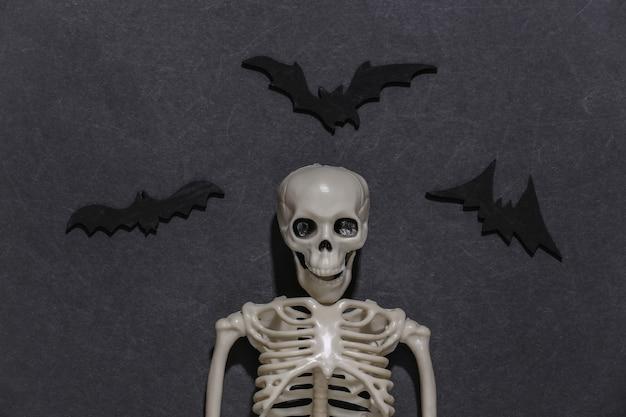 Esqueleto esculpido e morcegos em um fundo preto e escuro. tema de halloween.