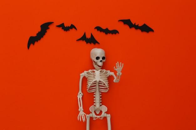 Esqueleto falso e morcegos em laranja brilhante. decoração de halloween, tema assustador