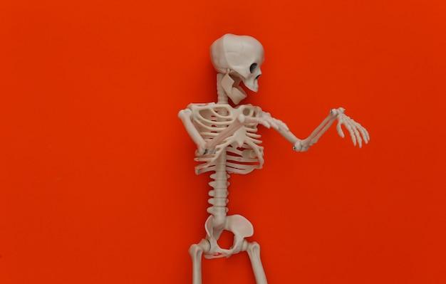 Esqueleto falso em laranja. decoração de halloween, tema assustador