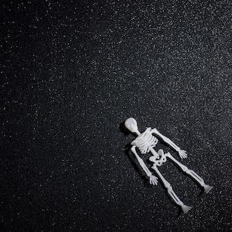 Esqueleto flutuante sobre fundo preto glitter