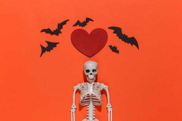 Esqueleto, morcegos e coração decorativo vermelho sobre um fundo rosa brilhante. dia dos namorados ou tema de halloween.