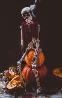 Esqueleto no halloween e abóboras laranja em uma superfície escura