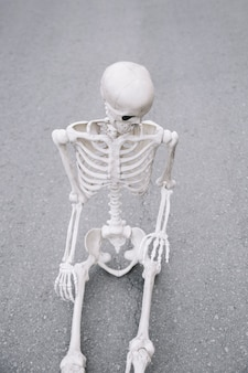 Esqueleto sentado na estrada e olhando para baixo