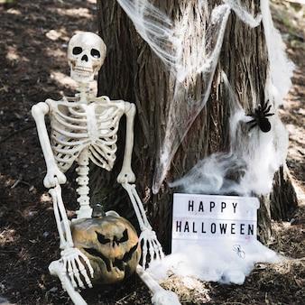 Esqueleto, sentando, perto, árvore, com, abóbora, e, feliz, dia das bruxas, inscrição