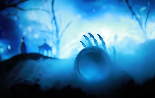 Esqueleto zombie mão saindo de um cemitério - halloween. previsões de bolas mágicas misteriosas e fumaça na cena escura. cartomante, poder da mente, conceito de previsão. fundo misterioso