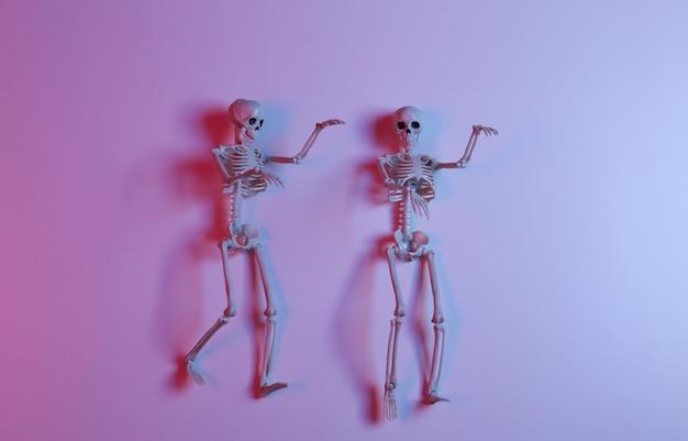 Esqueletos assustadores em luz de néon gradiente rosa azul