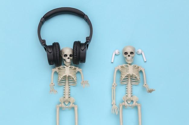 Esqueletos em fones de ouvido sobre um fundo azul. vista do topo