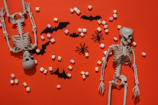 Esqueletos, pipoca, morcegos decorativos e aranhas em fundo laranja brilhante. composição de halloween