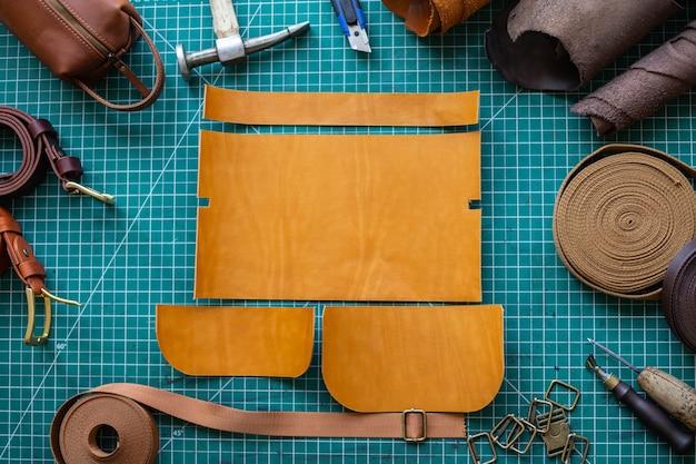 Esquema de corte de processo de bolsa com equipamentos e materiais curtidor masculino trabalhando em oficina de couro