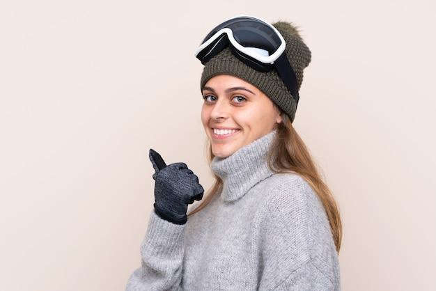 Esquiador adolescente com óculos de snowboard apontando para o lado para apresentar um produto
