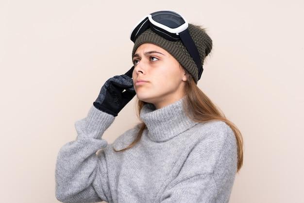 Esquiador adolescente com óculos de snowboard, tendo dúvidas e com a expressão do rosto confuso