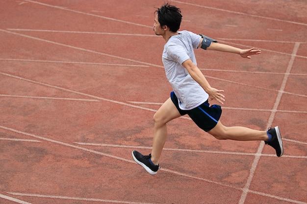 Esquiador atlético de corredor asiático que atravessa a linha de chegada.
