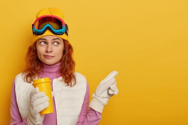 Esquiador com cabelo ruivo, usa chapéu amarelo, aponta para o lado no espaço em branco, segura café para viagem, demonstra paisagem de inverno, fica de pé contra fundo amarelo