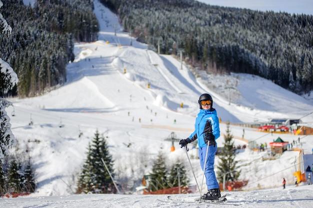 Esquiador de mulher contra pistas de esqui e teleférico em fundo