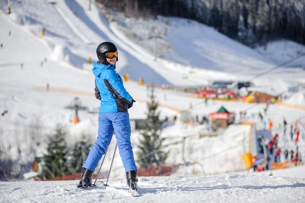 Esquiador de mulher em pé em uma pista de esqui em um dia ensolarado com animada estância de esqui e pistas de esqui no fundo