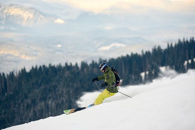 Esquiador descendo do pico da alta montanha coberto de neve