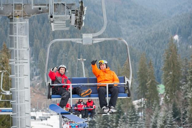 Esquiador e snowboarder subindo no teleférico