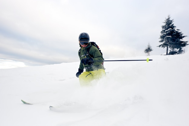 Esquiador em pó profundo em uma descida coberta de neve. conceito de esqui extremo. céu cinzento e pinheiro no fundo. vista frontal.