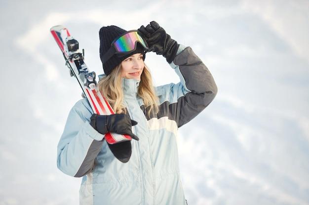 Esquiador em uma encosta de montanha posando contra um fundo de montanhas cobertas de neve