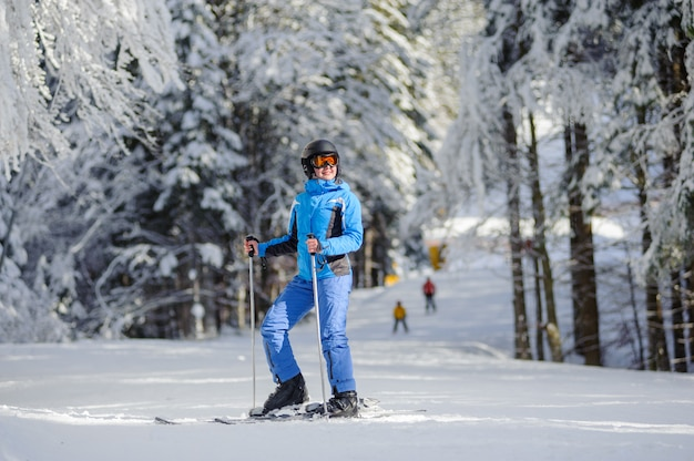 Esquiador feliz mulher numa pista de esqui na floresta