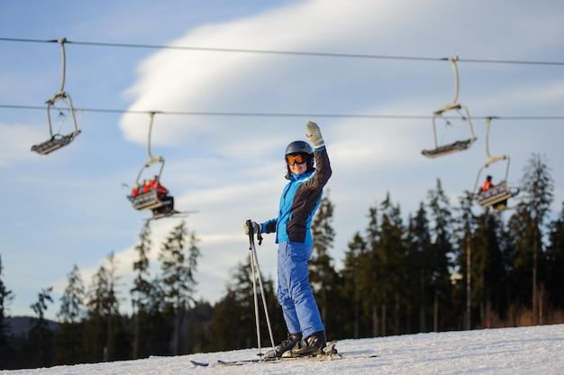 Esquiador feminino contra ski-lift e floresta em um dia ensolarado