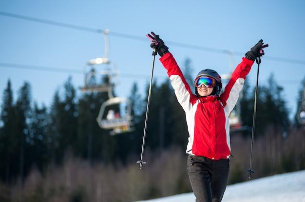 Esquiador feminino no declive nevado com as mãos levantadas