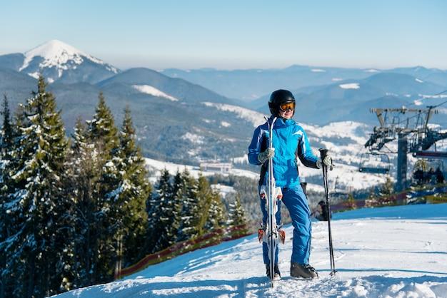 Esquiador feminino no sportswear de inverno posando no topo de uma montanha com seus esquis
