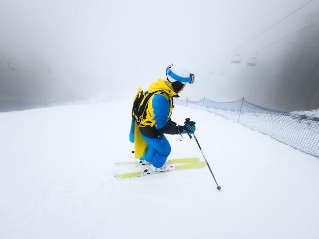 Esquiador jovem deslizando para baixo pelo espaço da cópia do tempo da névoa do inverno encosta nevada.