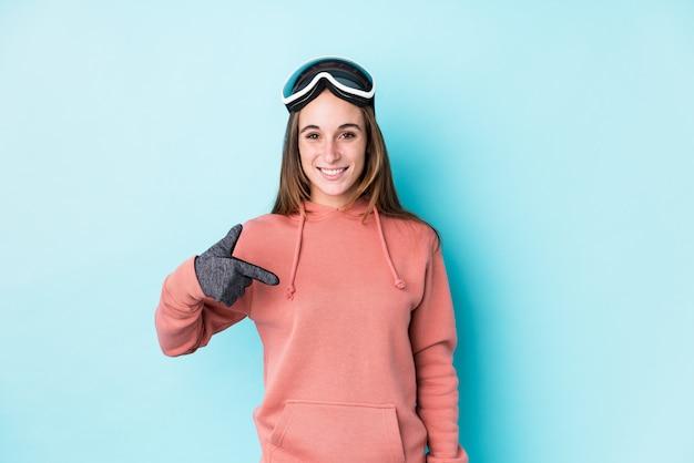 Esquiador jovem mulher isolada pessoa apontando à mão para um espaço de cópia de camisa, orgulhoso e confiante