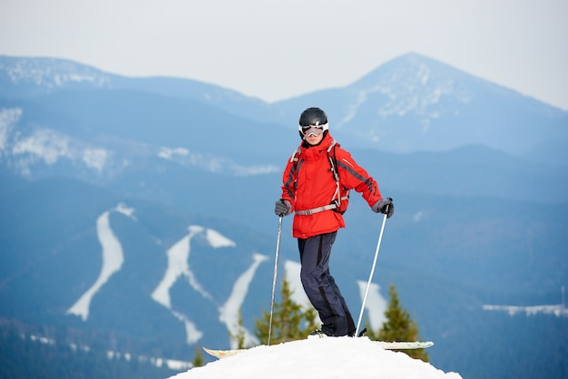 Esquiador masculino em pé no topo da encosta na estância de esqui de inverno