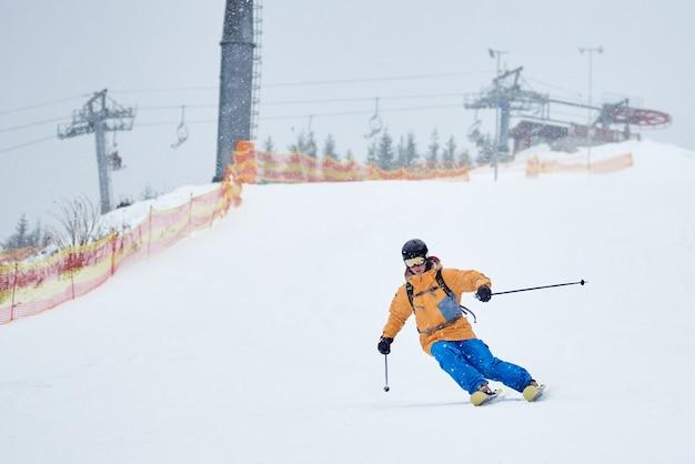 Esquiador masculino experiente esquiando na queda de neve, descendo uma encosta coberta de neve com rede na borda