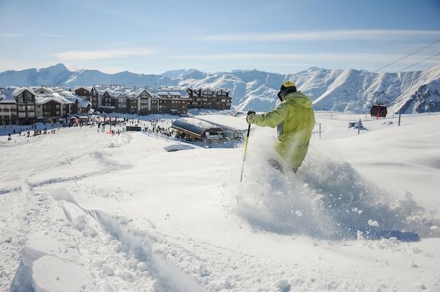 Esquiador no sportswear amarelo descendo a ladeira na geórgia, gudauri