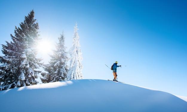 Esquiador no topo da montanha, apontando para o céu