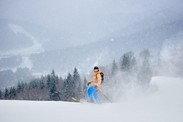 Esquiador posando em pé sobre esquis na neve profunda em pó em uma densa nevasca nas montanhas