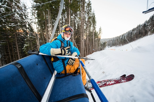 Esquiador profissional com esquis, sentado no teleférico, olhando para a câmera andando para o topo para descer da encosta no resort de inverno.
