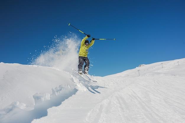 Esquiador profissional em sportswear amarelo brilhante pulando nas montanhas
