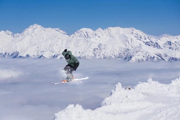 Esquiador voador em montanhas nevadas.