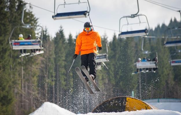 Esquiador voando sobre um obstáculo em dia de inverno