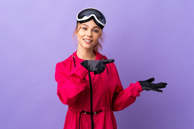 Esquiadora adolescente com óculos de snowboard sobre uma parede roxa isolada segurando copyspace imaginário na palma da mão para inserir