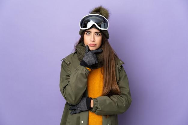 Esquiadora caucasiana com óculos de snowboard isolada em um fundo roxo pensando Foto Premium