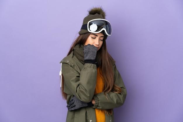 Esquiadora caucasiana com óculos de snowboard isolada no fundo roxo, tendo dúvidas