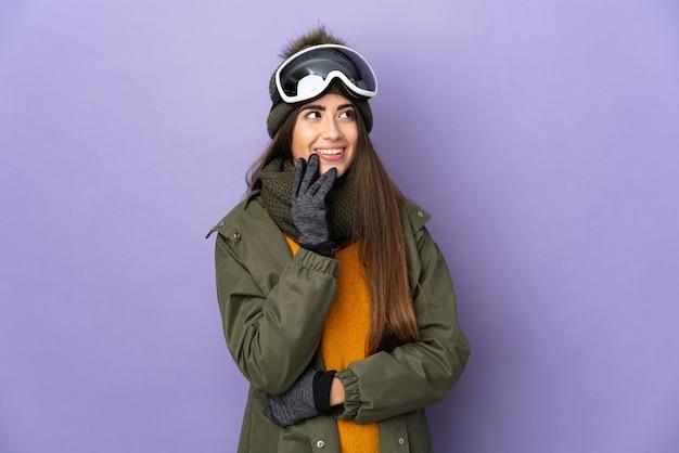 Esquiadora caucasiana com óculos de snowboard isolados na superfície roxa, olhando para cima enquanto sorri