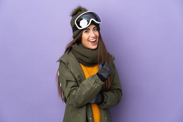 Esquiadora caucasiana com óculos de snowboard isolados no fundo roxo, comemorando uma vitória