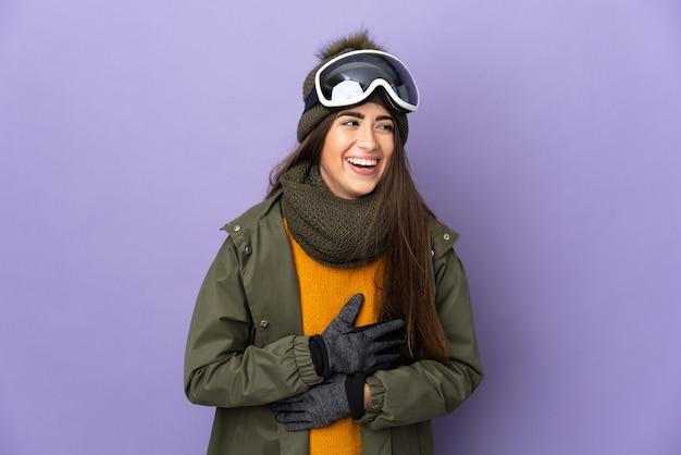Esquiadora caucasiana com óculos de snowboard isolados no fundo roxo e sorrindo muito
