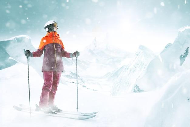 Esquiadora em pé com o céu em uma mão no fundo da bela paisagem montanhosa. inverno, esqui, neve, férias, esporte, lazer, conceito de estilo de vida