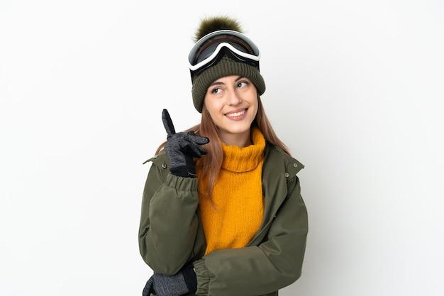 Esquiadora mulher caucasiana com óculos de snowboard isolados no fundo branco apontando para uma ótima ideia