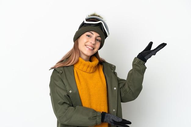 Esquiadora mulher caucasiana com óculos de snowboard isolados no fundo branco, estendendo as mãos para o lado para convidar a vir
