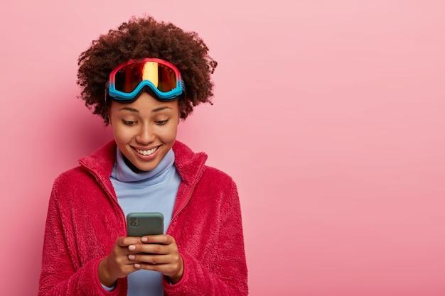Esquiadora ou snowboarder ativa olha com alegria para o celular isolado na parede rosa