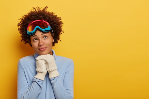 Esquiadora pensativa e encaracolada usa um macacão azul quente e luvas brancas, tem uma máscara de snowboard na cabeça e está contra um fundo amarelo.