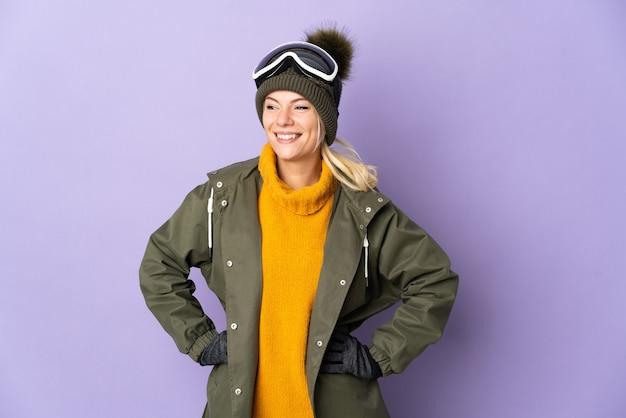 Esquiadora russa com óculos de snowboard isolado em um fundo roxo, posando com os braços na cintura e sorrindo